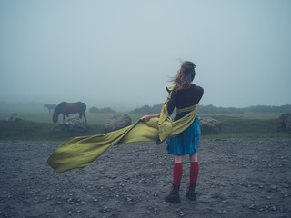 Woman with scarf in the wind looking at wild horses