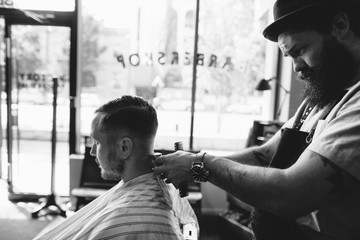 Stylish modern barber giving man a classic haircut - working on neckline