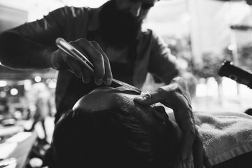 Detail of barber's hands giving man a classic hot lather shave - using straight razor