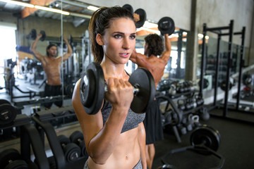 Serious determined motivational portrait of a confident strong female lifting weights