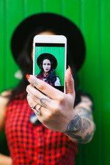 Portrait of a young alternative woman taking a selfie in front a green wall.