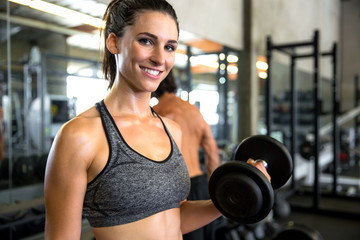 Cute smiling happy portrait of a beautiful woman in gym curling a dumbbell while exercising