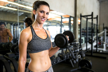 Commercial fitness model exercising at gym with weights showing strong core abs with a smile