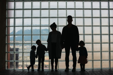 Sillouette of family standing together in front of window grid