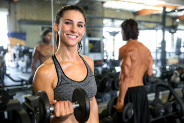 Cheerful happy portrait of a fit toned strong female lifting weight and exercising in coed gym