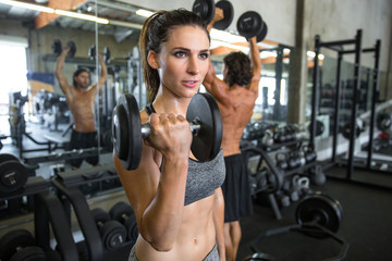 Men and women in local gym lifting weights building muscle showing intensity and determination