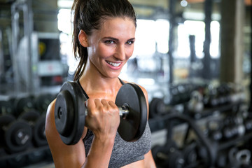 Commercial female model with perfect smile lifting weights curling dumbbell for toned fit arms