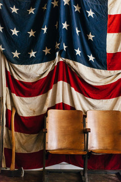 Large vintage American flag with an axe and old wooden seats.