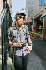 Hipster tourist holding a camera walking around sightseeing