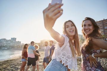Two happy male friends taking selfie on beach