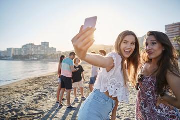 Two male friends taking selfie on beach by smartphone