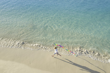 Aerial View of Little Boy Running Along Tropical Beach With Streamer on Vacation