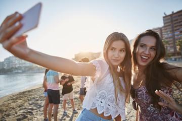 Two beautiful women taking selfie on beach having fun