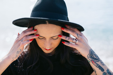 Portrait of a young alternative woman with tattoos and red nail polish.
