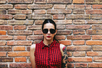 Young alternative woman standing in front a brick wall.