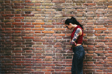 Side view of a young alternative woman standing in front a brick wall.