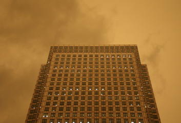 The sky turns red over buildings in Canary Wharf as dust from the Sahara carried by storm Ophelia filters sunlight over London