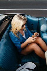 young teen female texting on mobile cell phone in back of convertible car in summer