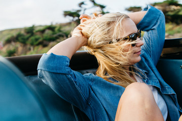 young blonde american female riding in back of blue convertible car with wind in hair