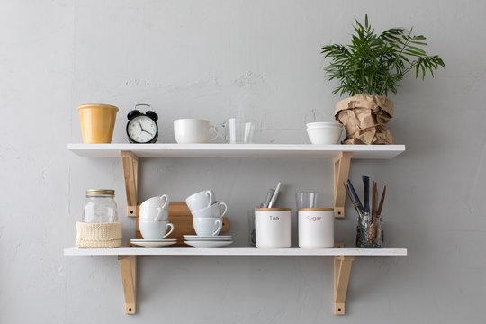 Utensils and mugs on shelf