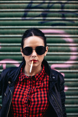 Portrait of a young alternative woman smoking in front a graffiti shutter door.