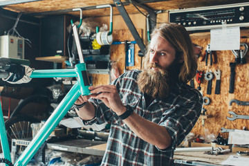 Bearded Bicycle Mechanic Taking Measurement on Fixed Gear Bike in Workshop