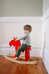 Young toddler boy rides a rocking moose and give the stink eye to the camera.