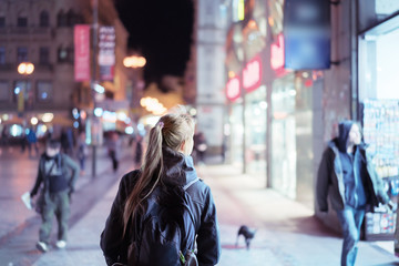 Fotomurales - Back view of girl walking on city street at night, Prague