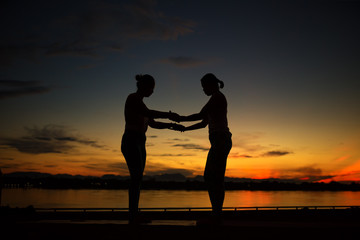 Silhouette young two women practicing yoga pose