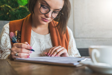Front view.Young businesswoman is sitting in coffee shop at table,signing documents.Student is studying online, doing homework.On table cup of tea. E-learning, education. Freelancer working, startup.