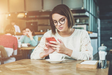 Young businesswoman is sitting in coffee shop at table and using smartphone, working. E-learning,online marketing,education.Hipster girl looking on screen of phone,checking email, blogging, chatting.