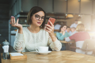 Young businesswoman is sitting in coffee shop at table and using smartphone, working. E-learning,online marketing,education. Hipster girl looking at phone screen in surprise, checking email, chatting.