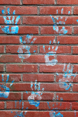 Blue hand prints on a brick wall