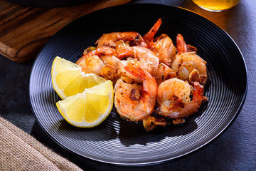 Skillet roasted jumbo shrimp on a black plate. Closeup. Shrimp roasted with sliced garlic and spices.