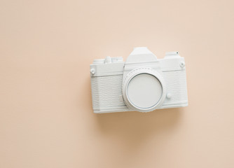 A painted white camera on cream color background