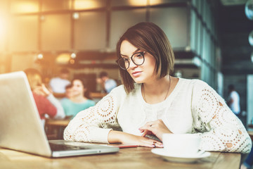 Young businesswoman in glasses sitting in cafe at table and working on laptop. Student is studying online. Hipster girl using computer. Online education, marketing, e-learning. Social media, network.