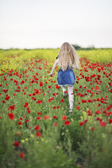 Happy girl running in poppy field