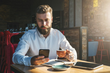 Young bearded businessman in white shirt is sitting in cafe at table, drinking tea and using smartphone. On desk is notebook and tablet computer.Online education, e-marketing, e-learning. Film effect.
