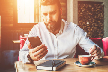 Young bearded businessman in white shirt is sitting in cafe at table,drinking tea and using smartphone.On desk is notebook.Man working, studying.Online education, e-marketing, e-learning. Film effect.