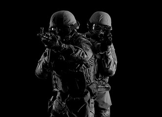 American soldiers in combat ammunition with weapons in the hands of equipped laser sights are in battle order.