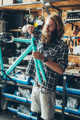 Long-Haired Hipster Mechanic Assembling Fixed Gear Bike in Bright Workshop