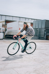 Hipster With Baseball Cap Racing on Fixed Gear Bicycle on Sunny Day