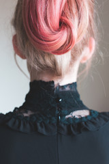 Back view of young woman with bright pink hair, wearing a high collared lace shirt