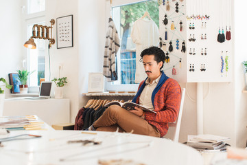 Young Latin Man Sitting in Bright Clothing Store and Reading a Magazine