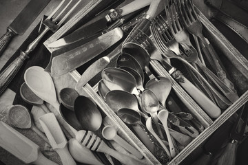 Vintage forks, spoons and knives in a dark old wooden box on a gray concrete or stone background. Selective focus.Black and white image.  Top view. Copy space.