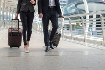business man and business woman walk together luggage on the public street, business travel