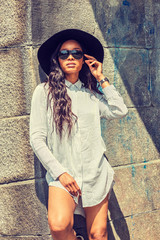 Young Mixed Race American Woman with long hair relaxing outside in New York, wearing white striped shirt, black sun hat, sunglasses, standing against wall on street under sun in summer..