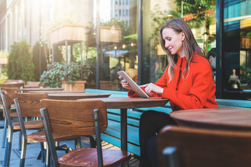 Side view. Young attractive woman in orange coat is sitting outside in cafe at table and uses tablet computer. Girl checking email, blogging, chatting, reading e-book. Social media, e-learning.
