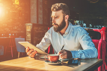 Young bearded businessman is sitting in cafe at table, holding tablet computer and writing in notebook. On desk is cup of tea and smartphone.Online education, e-marketing, e-learning. Film effect.