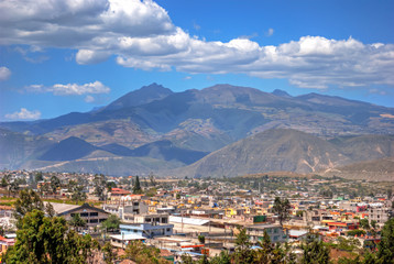 View of the Middle of the World town and the Andes mountains in the background, on a sunny and cloudy summer morning, Ecuador.